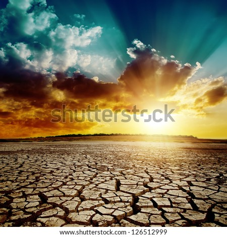 global warming. dramatic sunset over cracked earth - stock photo