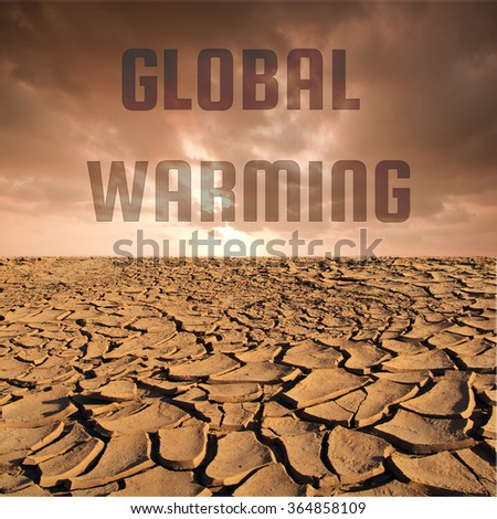 Global warming word on Cracked dry land without water and red sky background for Global warming concept - stock photo