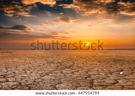 Global worming concept - cracked scorched earth soil drought desert landscape dramatic sunset - stock photo