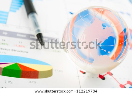 Global year report with glass globe and pen