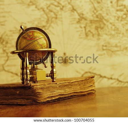 Globe and vintage book against map on a wall. - stock photo