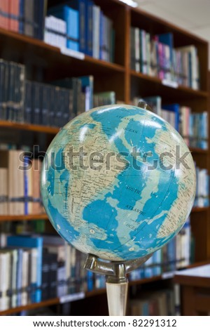 Globe ball in library with blurr background - stock photo