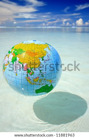 Globe floating in exotic sea - stock photo