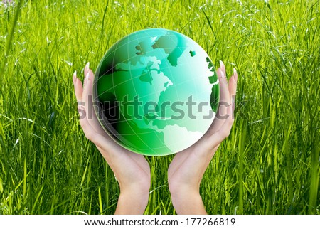 Globe Green Planet Earth in hands Woman on the fresh green grass background