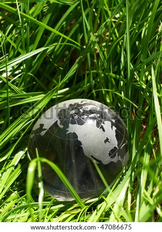 Globe in a grass, ecology - stock photo