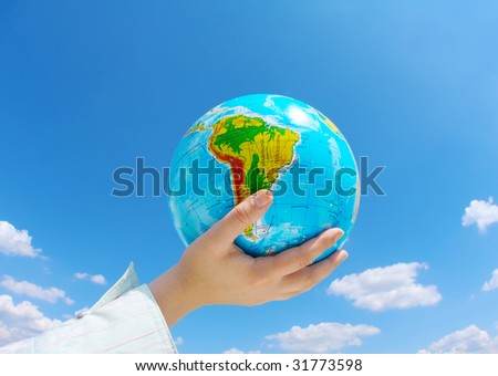 globe in hands under blue sky