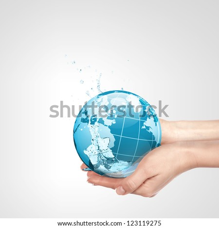 Globe in human hand against blue sky. Environmental protection concept. Elements of this image furnished by NASA