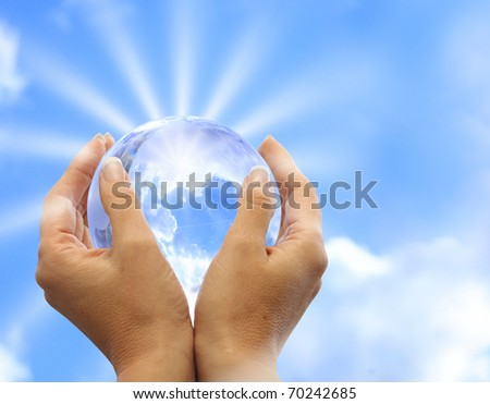 Globe in human hand against sun and blue sky. Environmental protection concept. - stock photo