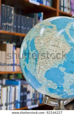Globe in library with blurred background - stock photo