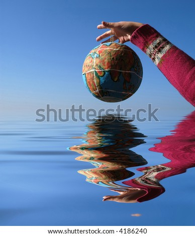 globe in the hand, with reflection in the water - stock photo