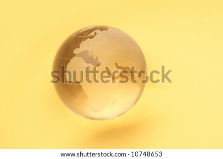 globe isolated on yellow background with reflection - stock photo