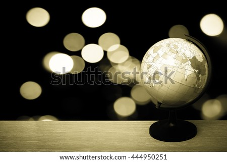 Globe model on desk with bokeh from light in city background