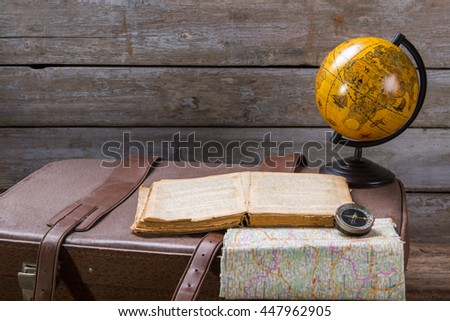 Globe next to opened book. Compass and book on suitcase. Captain's journal with important notes. Story of the expedition. - stock photo
