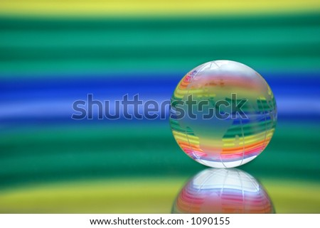 Globe on a surface of a mirror. On a multi-coloured background. - stock photo