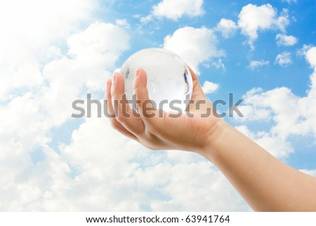 Globe on child hand against blue sky - stock photo