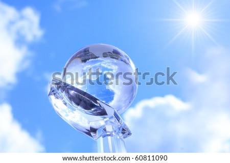 Globe on cristal hand against blue sky. - stock photo
