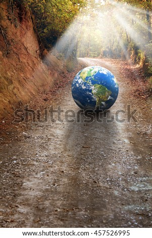 globe on dirt road in forest. Furnished NASA globe image used for this image. - stock photo