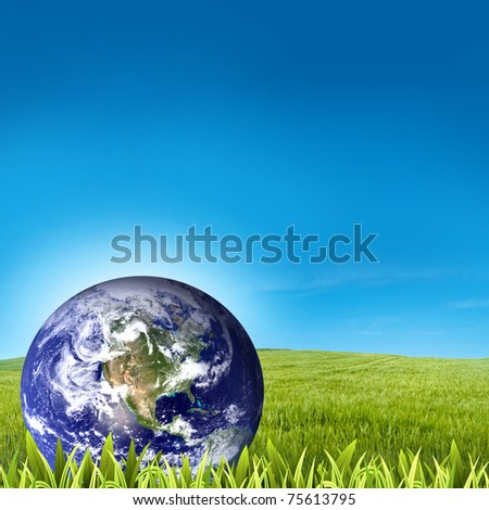 Globe on green grass with blue sky background - stock photo