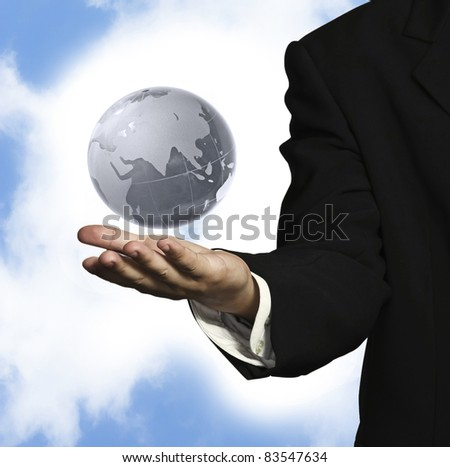 globe on hand of businessman and sky background