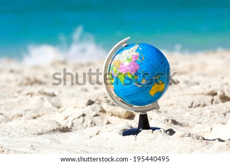 Globe on tropical beach, travel concept  - stock photo