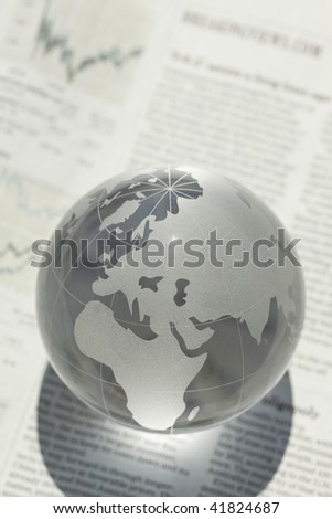 Globe put in newspaper - stock photo