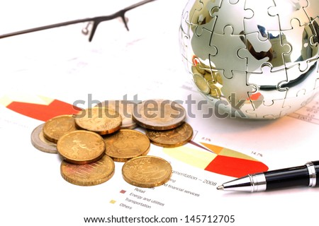 Globe puzzle and Euro coins on business document  - stock photo