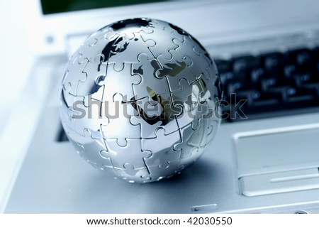 Globe puzzle on laptop - stock photo