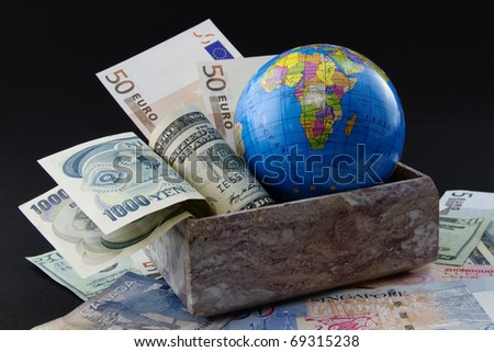 Globe with world currencies in marble box and placed on world currency - stock photo