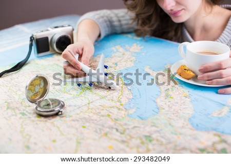 Globetrotter coffee break for trip dreams. A woman sitting at table with a map with toy airplane, compass and camera and visualises his desire to travel. Shallow depth of field - stock photo