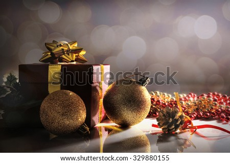 Gloom Christmas decoration on a white table methacrylate. With red gift box with gold ribbon, two golden balls and pearls. Front view. Horizontal composition.