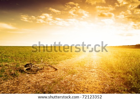 Gloomy dawn on rural road in field. Bicycle. - stock photo