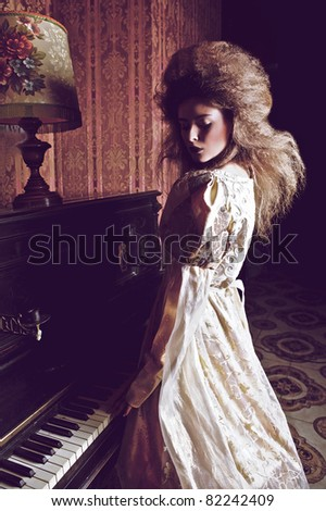 Gloomy duchess near old piano. Vogue style vintage portrait in luxury interior. - stock photo
