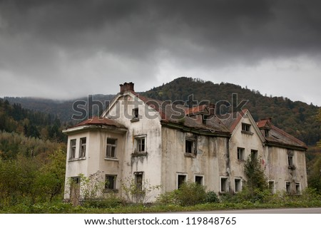 Gloomy house in the mountain forest - stock photo
