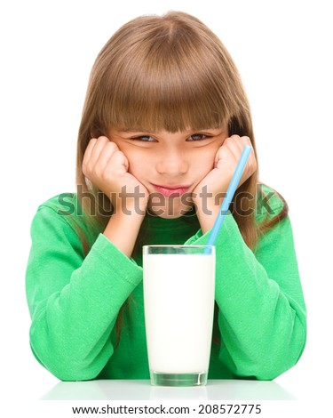 Gloomy little girl does not want to drink milk, isolated over white - stock photo