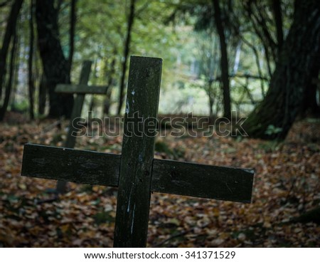 Gloomy, neglected cemetery with wooden cross in the foreground. - stock photo