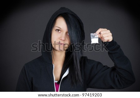 Gloomy portrait of a young woman or teen addict looking sad showing her little bag of drugs. - stock photo