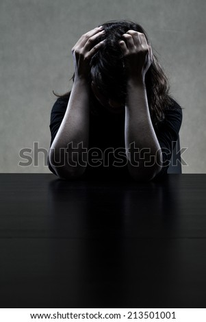 Gloomy portrait of depressed woman sitting at the table - stock photo