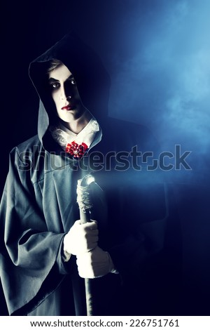 Gloomy, scary vampire in a black cloak hiding his face under a hood. Halloween.