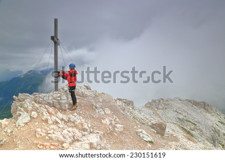 Gloomy sky and climber opening the metal box attached to the cross on the summit of Averau peak, Dolomite Alps, Italy - stock photo