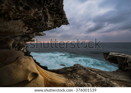 gloomy stormy seascape sunrise with cliff protrusion and dark skies