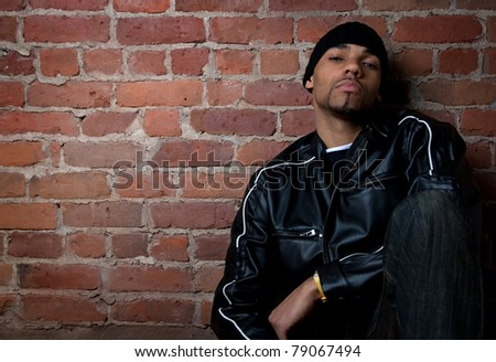 Gloomy street guy dressed in black, sitting near a brick wall. - stock photo