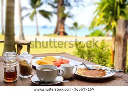 Glorious early morning breakfast at the beach resort in Thailand : freshly brewed black coffee, pancake, maple syrup, fresh fruits. Tropical vegetation and the sea visible on the background.  - stock photo