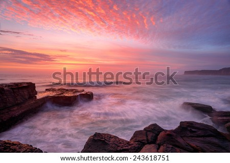 Glorious summer sunrise skies over North Avoca rockshelf and a soft sea spray mist and motion in the waves.  NSW Australia - stock photo