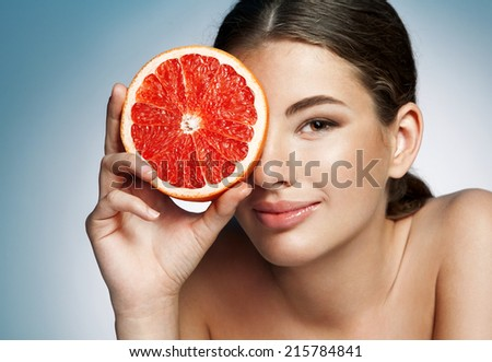 Glossy girl with grapefruit cut in half fruit in hand / photoset of attractive girl holding a cut piece of Sicilian orange on blue background  - stock photo