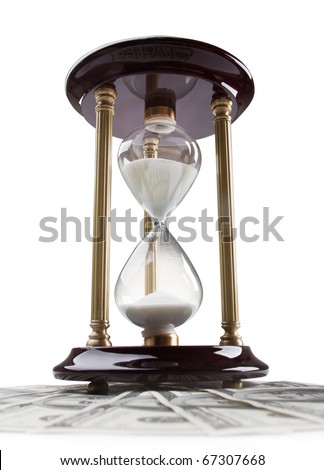 glossy old-style hourglass standing on american hundred dollar bills
