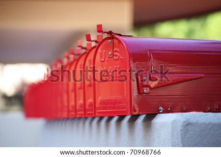 glossy red mailbox repetition in american style and blurred background for mails - stock photo