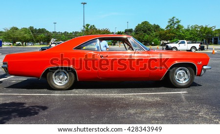 GLOUCESTER, VA - MAY 28, 2016: A red 1965 Chevrolet Impala SS 396 at the First Aaron's rental car and Motorcycle show, the show is Sponsored by Aaron's furniture rental of Gloucester   - stock photo