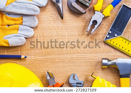 glove cutter monkey wrench pliers ruller hammer tapeline nippers helmet pencil with small copyspace on wooden board construction concept  - stock photo