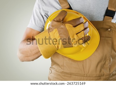 Glove. Workman wearing a protective glove holding a yellow hardhat or safety helmet conceptual of a builder, construction worker, tradesman or manual labourer - stock photo