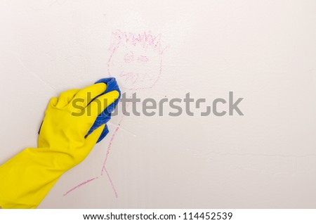 Gloved hand, cleaning crayon off wall with cloth - stock photo